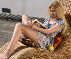 Girl sitting in wicker chair reading book Stock Photo