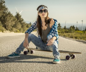 Girl sitting on skateboard listening to music Stock Photo