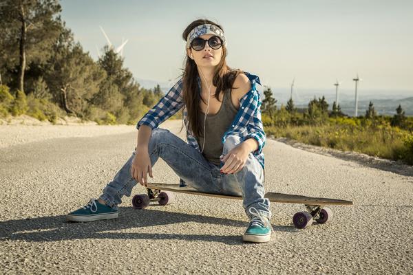 Girl sitting on skateboard listening to music Stock Photo