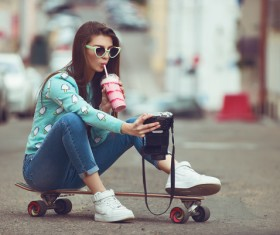 Girl sitting on skateboard selfie Stock Photo
