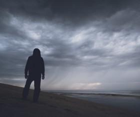 Man standing alone on beach Stock Photo