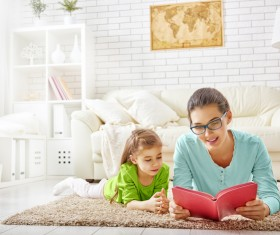 Mother and daughter reading together in the living room Stock Photo 01