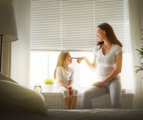 Mother and daughter sitting on the windowsill happy Stock Photo
