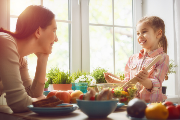 Mother looks at the daughter who makes the salad Stock Photo
