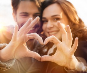 Romantic lovers make heart gesture Stock Photo