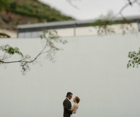 Romantic marriage couple posing near white wall Stock Photo
