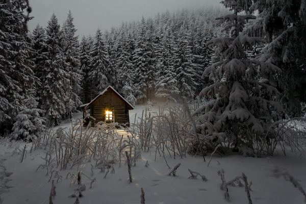 Snow covered cottage in the forest Stock Photo