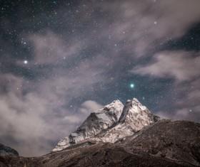 Sparkling starry sky above rocky mountain Stock Photo