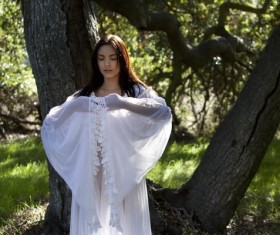Woman in white dress meditating in the woods Stock Photo