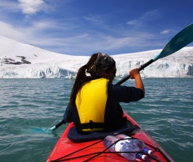 Woman in winter paddling boat Stock Photo
