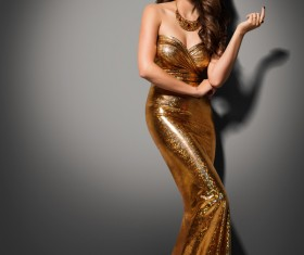 Woman wearing a gold evening gown Stock Photo