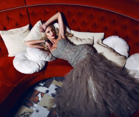 Woman wearing evening dress lying on sofa Stock Photo