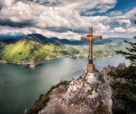 Wooden cross on high rocky peak landscape Stock Photo