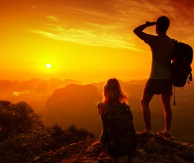 Young Lovers on the top of the mountain looking at sunrise Stock Photo
