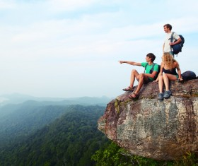 Young climber sitting on the mountain top Stock Photo