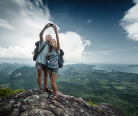 Young couple taking pictures on the mountain top Stock Photo