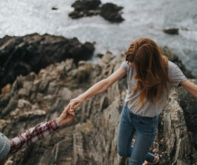 Young couple walking on rocky beach Stock Photo