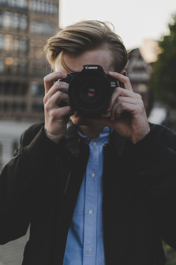 Young man taking photo with digital camera Stock Photo ...