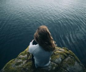 Young woman looking at calm lake Stock Photo