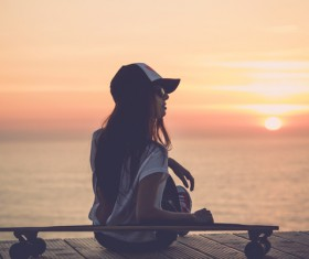 girl leaning on the skateboard watches sunrise Stock Photo