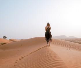 woman walking on dunes desert Stock Photo