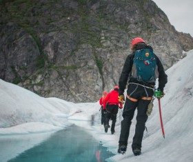 Backpacker walking on iceberg Stock Photo