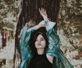 Beautiful asian girl leaning on tree trunk Stock Photo