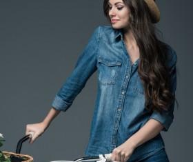 Beautiful woman wearing denim suit pushes bicycle Stock Photo 02