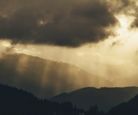 Black clouds and sun rays on mountain Stock Photo