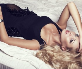 Blonde in black dress lying on the bed Stock Photo