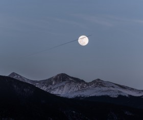 Bright moon above snowy mountain range Stock Photo