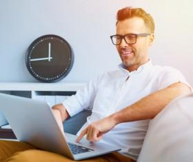 Casual man relaxing using laptop Stock Photo 04
