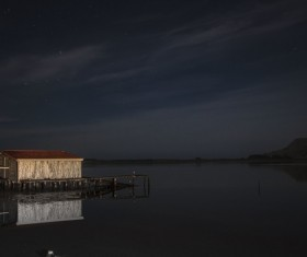 Cottage on calm river at twilight Stock Photo