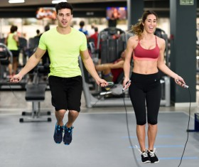 Couple doing jump rope exercises in gym Stock Photo