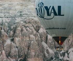 Flying hot balloon above rocky mountain landscape Stock Photo