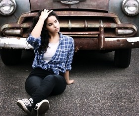 Girl sitting in front of old car Stock Photo