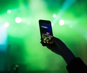 Hand taking photo with smartphone in music party Stock Photo
