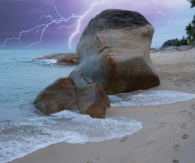 Lightning with seaside boulders landscape Stock Photo