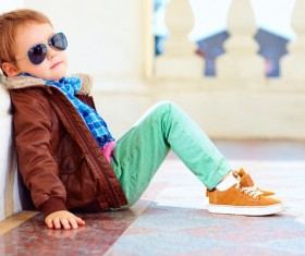 Little boy with sunglasses sits on the floor Stock Photo