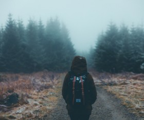 Lonely backpacker walking on misty pathway Stock Photo