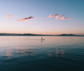 Lonely persone rowing on empty calm beach Stock Photo