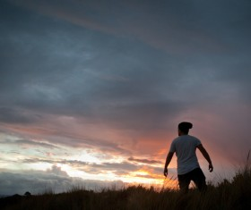 Man on the meadow at dusk Stock Photo