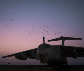 Man performing standing on airplane roof at dusk Stock Photo