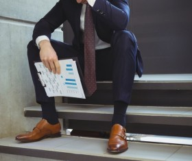 Man sitting on steps hands holding business report Stock Photo