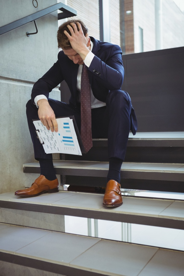 Technology Management Image: Man Sitting On Steps Hands Holding Business Report Stock