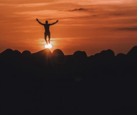 Man with artistic pose standing on sun Stock Photo