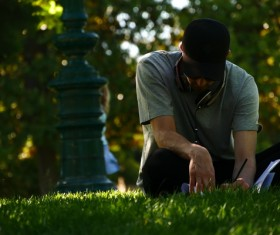 People sitting in the grass to write things Stock Photo