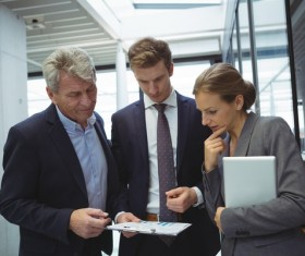 People viewing business reports together Stock Photo