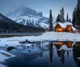 Reflection cottage on frozen winter lake Stock Photo