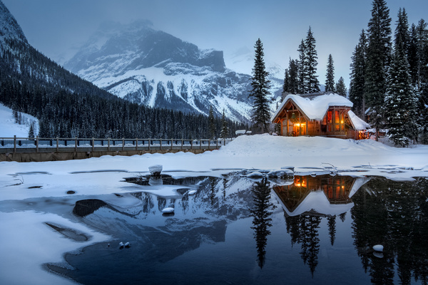 Reflection cottage on frozen winter lake Stock Photo